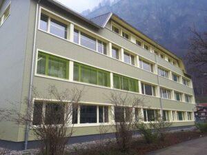 Schulhaus mit Eternitfassade grün